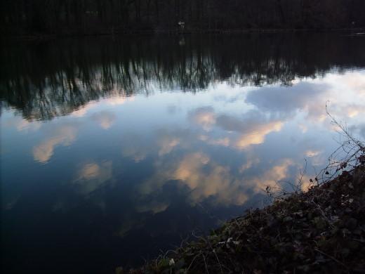 Abendwolken und Bäume spiegeln sich im Fluss
