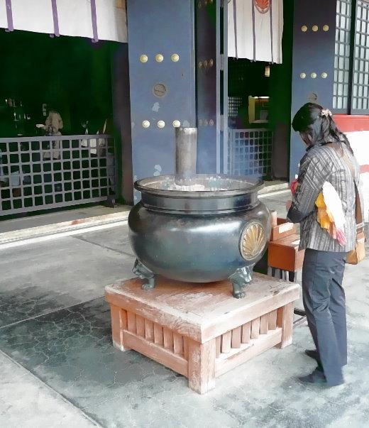 Rauchbecken mit dem aufsteigenden Rauch von Räucherstäbchen vor dem Eingang zum Kurama-Haupttempel.