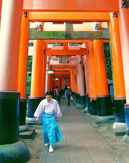 Ein Helfer beim Inari-Fest in ritueller Kleidung eilt in einem Torii Tunnel den Berg hinab!