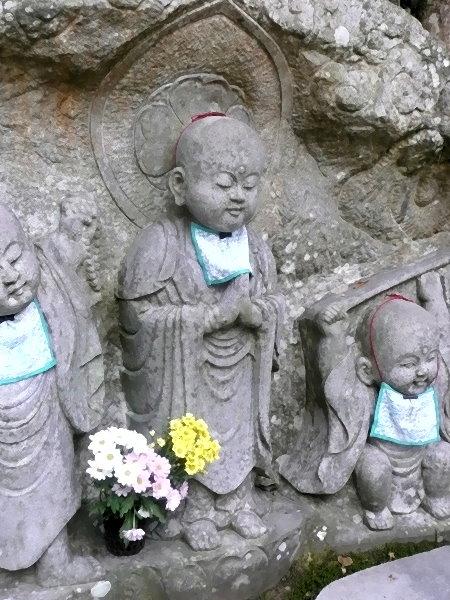 Wesenheit in Gebetshaltung und mit Heiligenschein im Mittelpunkt des Shinto-Schreines der Kinder-Kamis!