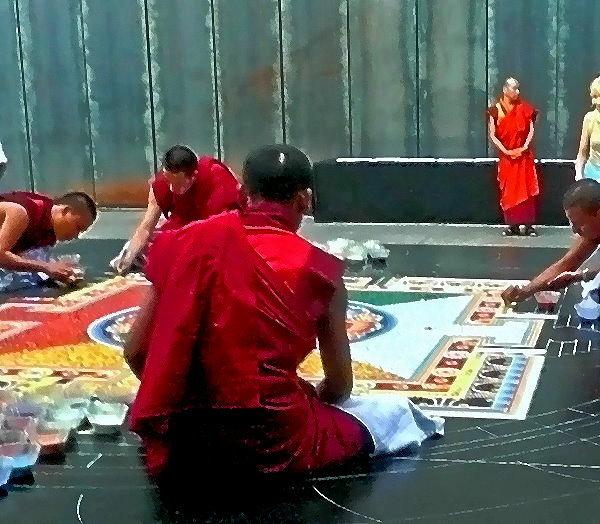 Vier Mönche aus Bhutan streuen in der Jahrhundert-Halle in Bochum ein Mandala